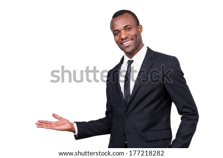 Welcome! Handsome young African man in formalwear gesturing and smiling while standing isolated on white background  - stock photo