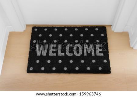 Welcome home doormat with close door - stock photo