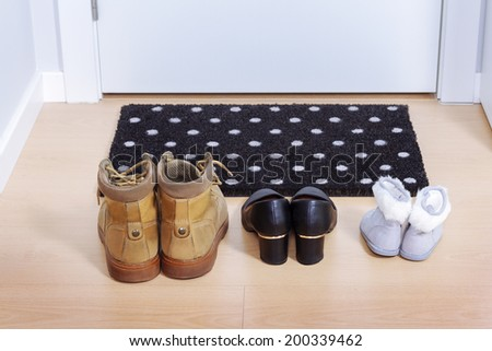 Welcome home doormat with shoes - stock photo