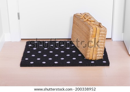 Welcome home doormat with suitcase - stock photo