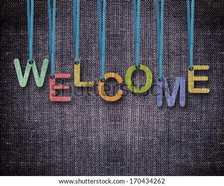 Welcome Letters hanging strings with blue sackcloth background. - stock photo