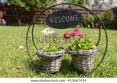 Welcome mat pancard with colorful flowers, green grass in a family garden atmosphere.  Perfect beckground for any image. - stock photo
