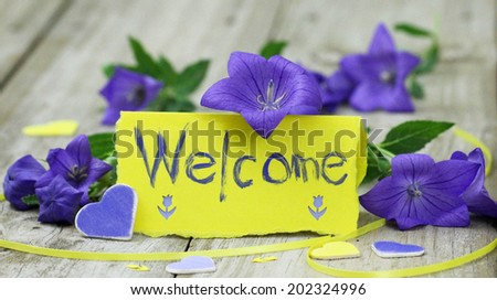 Welcome note card on wood table with purple flowers and hearts - stock photo