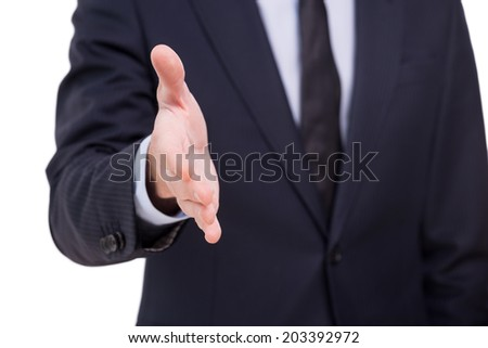 Welcome on board! Close-up of businessmen stretching out hand for shaking while standing against grey background