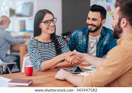 Welcome on board! Confident young woman and man shaking hands and smiling while sitting at the desk in office - stock photo