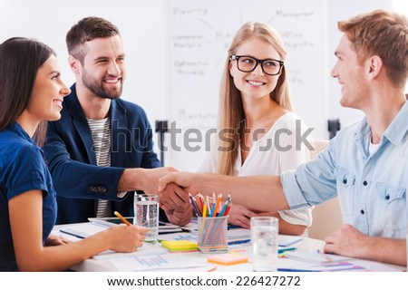 Welcome on board! Group of cheerful business people sitting at the table together while two men shaking hands and smiling  - stock photo