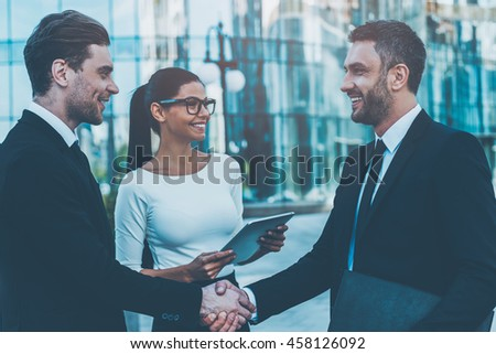 Welcome on board! Two happy young businessmen shaking hands while their female colleague holding digital tablet and smiling