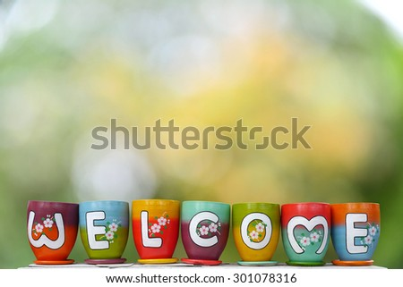 welcome on colorful earthenware jar in nature bokeh background - stock photo