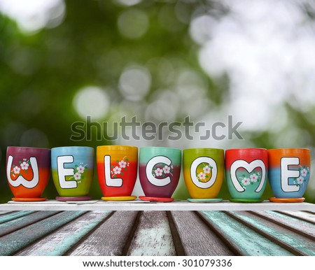 welcome on colorful earthenware jar in nature bokeh background
