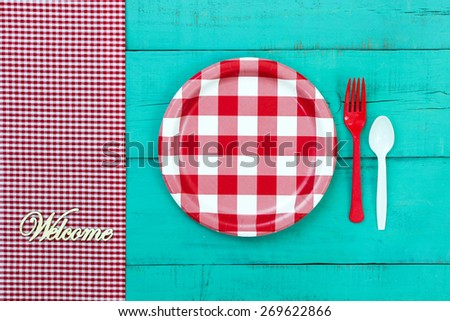 Welcome sign by red and white checkered picnic plate with gingham tablecloth on antique teal blue wooden table; above view looking down - stock photo