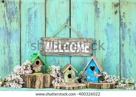 Welcome sign hanging over colorful birdhouses with butterfly on cedar logs by spring tree blossoms on antique rustic mint green wood background - stock photo