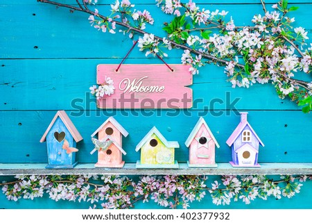 Welcome sign hanging over colorful birdhouses with butterfly on shelf by spring tree flowers on antique rustic teal blue wood background; pink, yellow, purple, orange birdhouses - stock photo