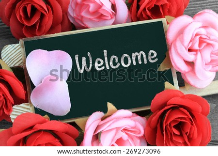 welcome sign on chalkboard, with flowers in background - stock photo