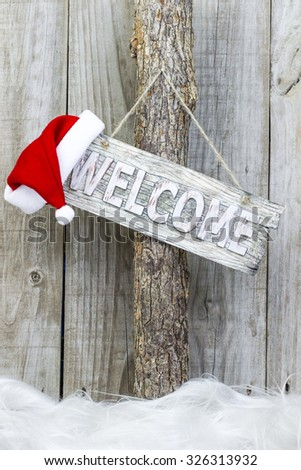Welcome sign with Santa Claus hat hanging on tree with rustic antique wooden background