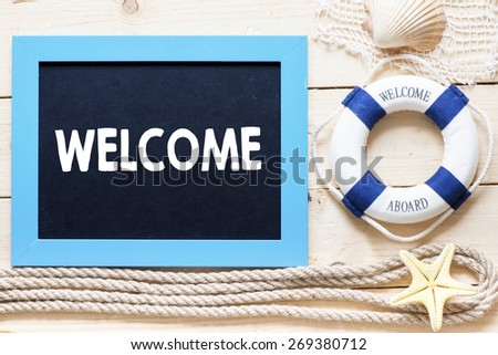 Welcome Text written on blackboard with starfish - stock photo