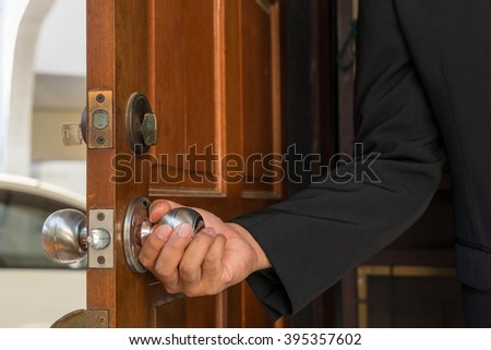 welcome to home by man and open wood door for you - stock photo