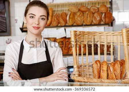 Welcome to my shop! Shot of a beautiful female baker posing in the bakery store  - stock photo