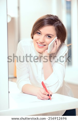 Welcome to our salon. Portrait of a beautiful smiling administrator of hairstyle salon speaking over the mobile phone and putting down details of the order   - stock photo