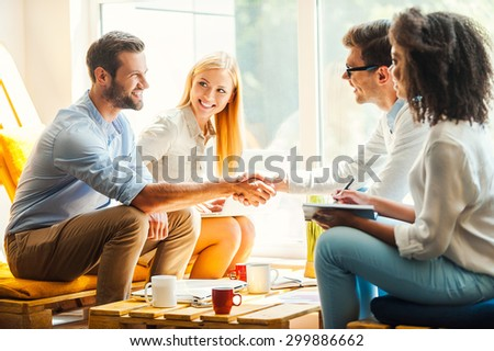 Welcome to our team! Two happy young womenworking togetherat the rest area while two men shaking hands and smiling  - stock photo