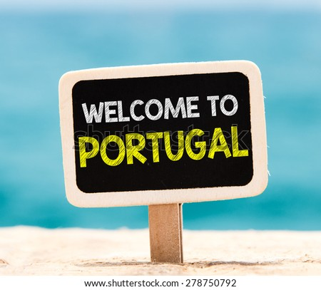 Welcome to Portugal on chalkboard. Welcome to Portugal text written on chalkboard, on beach - stock photo