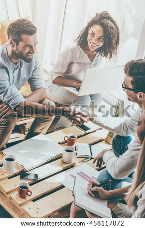 Welcome to team! Two cheerful young men sitting at the wooden desk in office and shaking hands while two beautiful women looking at them and smiling