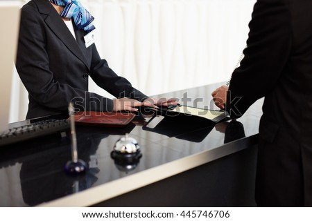 Welcome to the hotel. Male and female receptionists standing at the front desk - stock photo