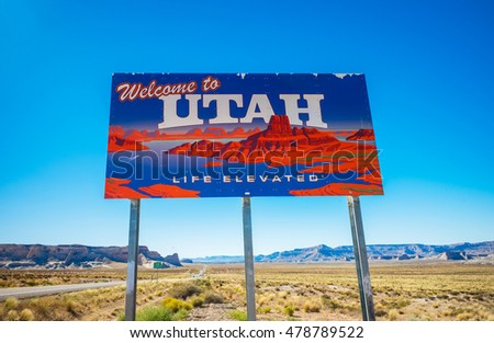 Welcome to Utah sign on a desolate desert highway against a blue sky