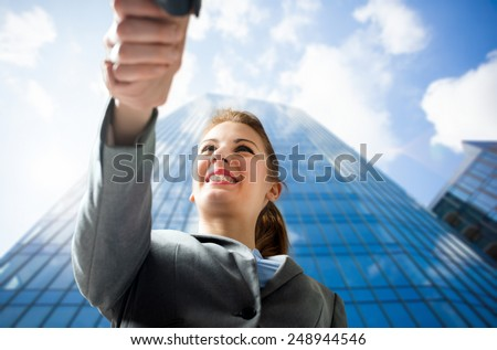 Welcoming business woman giving a handshake and smiling - stock photo