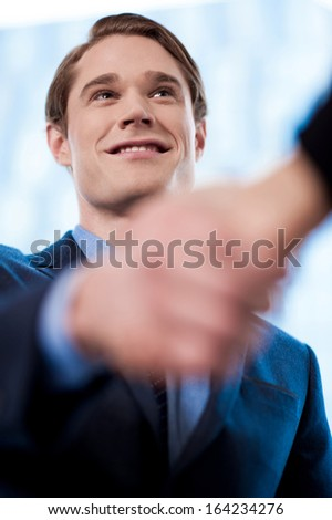 Welcoming businessman gives a handshake - stock photo