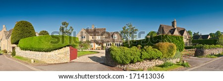 Welcoming family homes with well manicured hedges, gardens and pretty drystone walls, clear blue sky and warm early morning sunlight. Stitched panoramic image. - stock photo