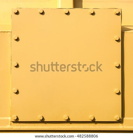 Welded and bolted metal plates painted with yellow colors. Closeup view. Free square shape space to enter a text.
