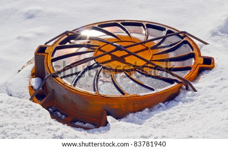welded sewer lid in snow field - stock photo