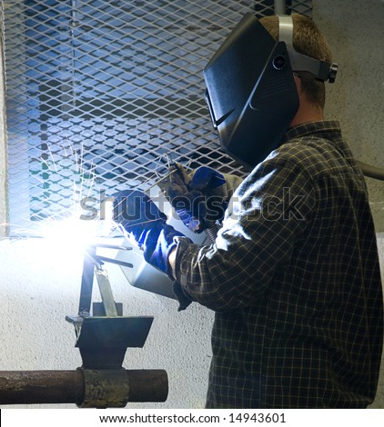 Welder at work, illuminated by an acetylene welding torch.  All work depicted is authentic and in compliance with industry code and safety regulations. - stock photo