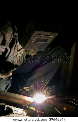 welder at work with electrode and welding arc