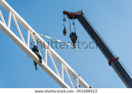 Welder climbing high on the steel structure on height and placing truss lifted by crane for installation work