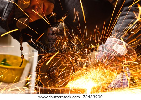 Welder cutting iron with sparks - stock photo