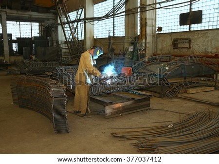 Welder in factory. Worker weld metal in factory and sparks - stock photo