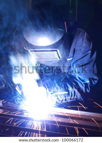 Welder in protection and sparks. Production and construction. - stock photo