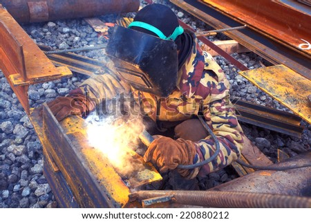 Welder in protective mask welding metal construction on open air. - stock photo