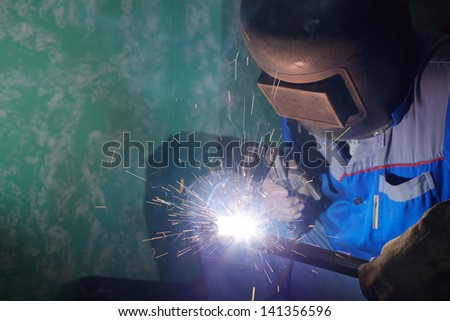 Welder in protective suit and mask welds metal pipes - stock photo
