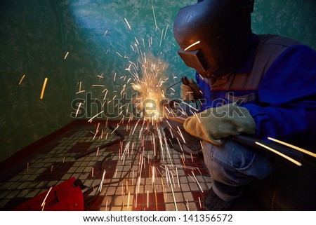 Welder in protective suit and mask welds metal pipes on staircase and sparks scatter around - stock photo