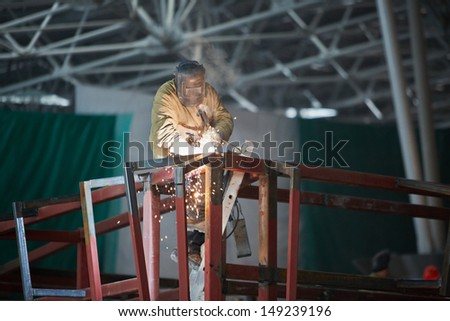 Welder in protective suit and mask welds steel frame standing on stepladder - stock photo