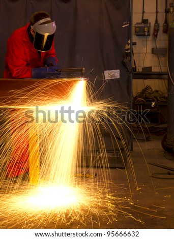 Welder in workshop manufacturing metal construction by cutting to shape using huge orange sparks - stock photo