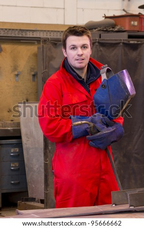 Welder in workshop manufacturing metal construction looks at camera and holds helmet and torch - stock photo
