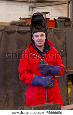 Welder in workshop manufacturing metal construction looks at camera whilst carrying torch and wearing overalls and safety visor. - stock photo