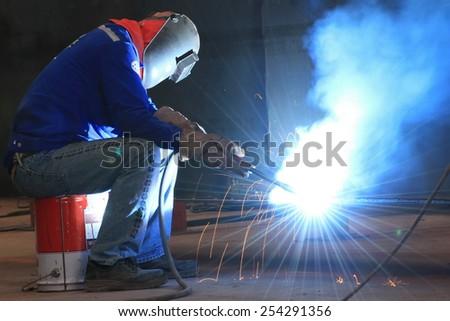 welder is welding steel part - stock photo