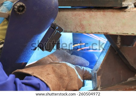 welder is welding steel structure with all safety equipment - stock photo