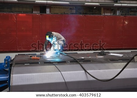 Welder man in work welding a steel sheet by TIG or WIG welding procedure, using a welding wire and inert gas. Hard and heavy work in steel factory. Heavy industrial production of steel construction.