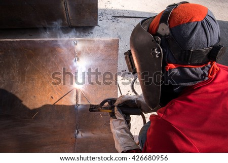 Welder man welding metal and sparks ,Mask and gloves for protection.