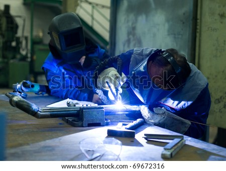 Welder master with trainee at work - stock photo